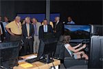 Ribbon cutting attendees observe a student learning on the new educational driving simulators.